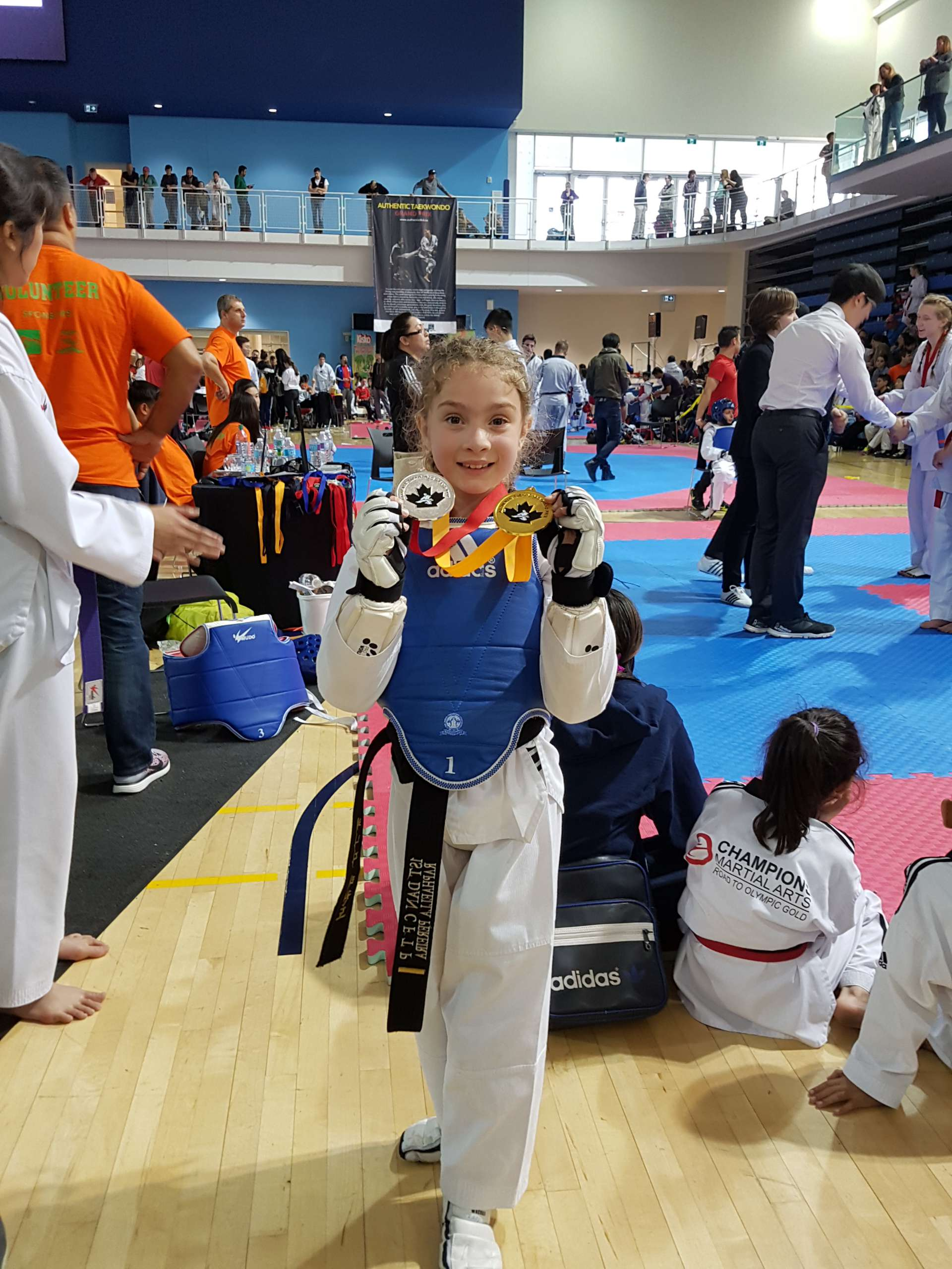 young girl showing medals won from black belt taekwondo tournament